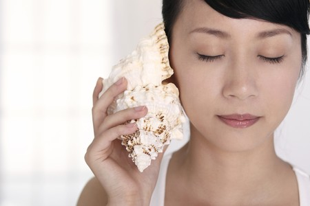 eyes closing: Woman holding seashell to ear while closing her eyes