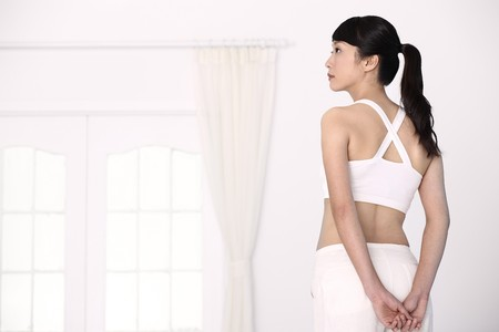 Woman standing with hands clasped behind her backs Stock Photo - 4194527