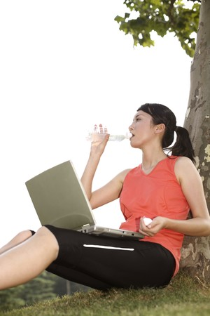 Woman drinking water while working with laptop in the park photo