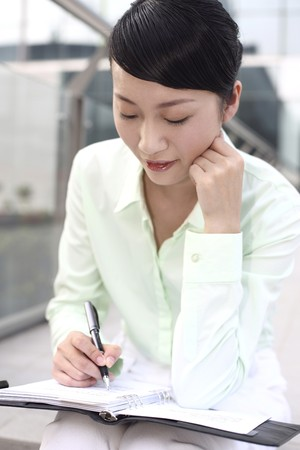 Businesswoman writing in organizer photo