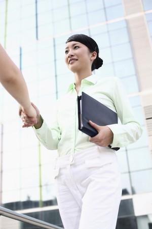 Businesswoman shaking hands with organizer in one hand