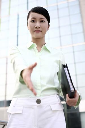 extending: Businesswoman extending hand for handshake Stock Photo