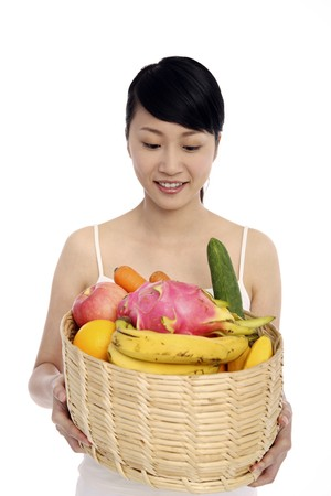 Woman holding a basket of fresh fruits and vegetables Stock Photo - 4194513