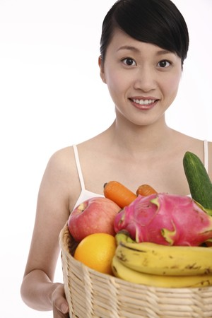 Woman holding a basket of fresh fruits and vegetables Stock Photo - 4194432