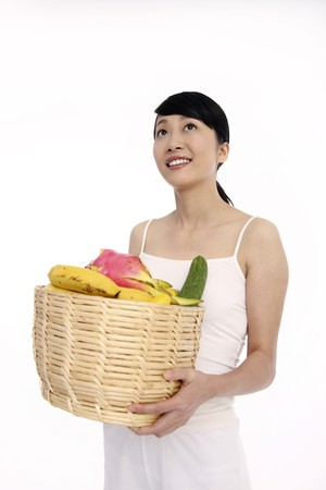 Woman holding a basket of fresh fruits and vegetables, looking away photo