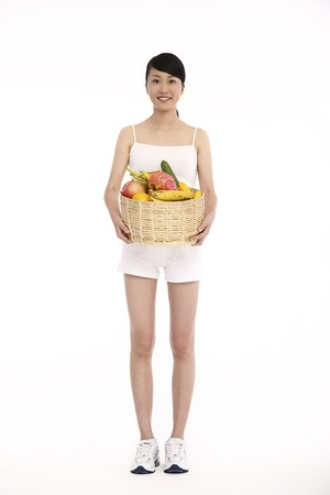 Woman holding a basket of fresh fruits and vegetables photo