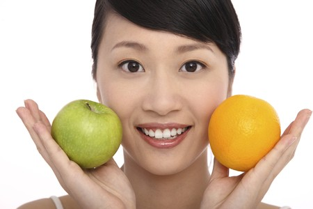 Woman holding apple and orange in each hand Stock Photo - 4194254