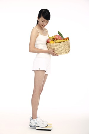 Woman holding a basket of fresh fruits and vegetables, standing on scale photo