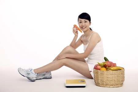 Woman holding carrot with scale and a basket of fresh fruits and vegetables at her side photo