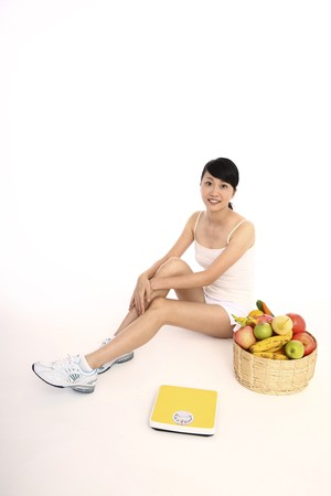 Woman sitting with scale and a basket of fresh fruits and vegetables at her side photo