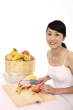 Woman cutting dragon fruit photo