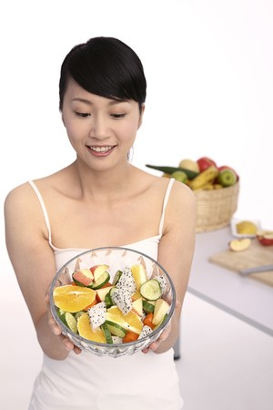 Woman holding a bowl of fruit salad photo