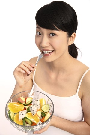 Woman holding a bowl of fruit salad, biting fork photo