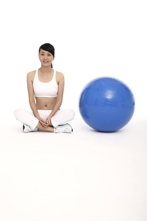 Woman sitting beside fitness ball photo