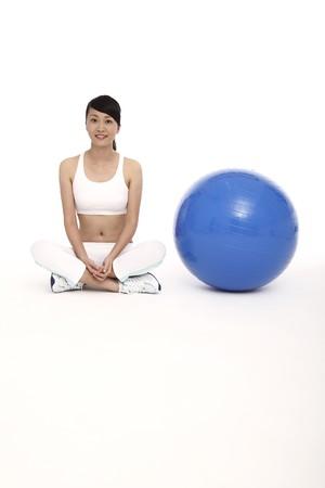 Woman sitting beside fitness ball photo