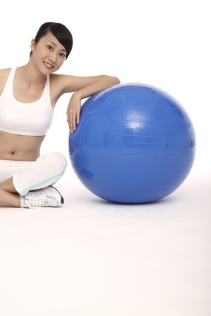 Woman resting one arm on fitness ball photo