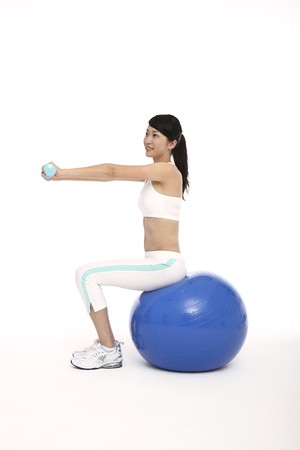 Woman exercising on fitness ball while lifting weights photo