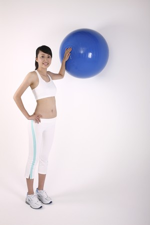 Woman holding fitness ball against the wall Stock Photo - 4194510