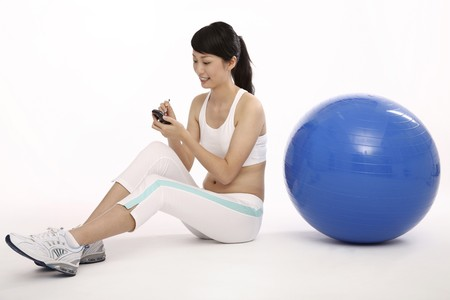 Woman using pda, fitness ball at the side photo