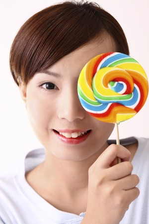Woman holding a lollipop over her left eye