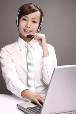 Businesswoman using laptop while talking on headset photo