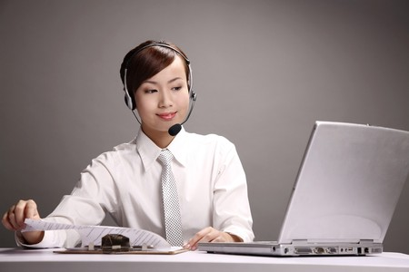Businesswoman wearing headset checking documents on clipboard Stock Photo - 4194651