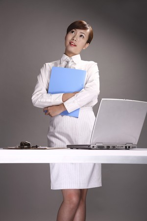 Businesswoman holding a file, contemplating photo