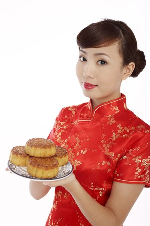 Woman wearing cheongsam holding a plate of mooncakes Stock Photo - 4194738