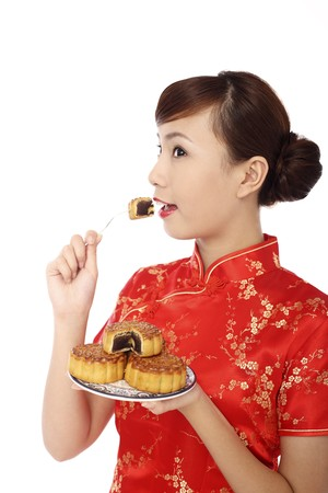 Woman wearing cheongsam eating mooncake photo