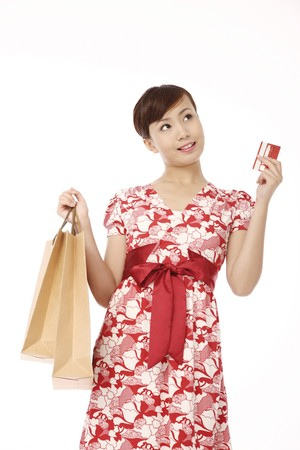 Woman holding a credit card and shopping bags Stock Photo