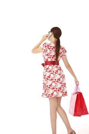 Woman holding shopping bags and talking on the phone photo