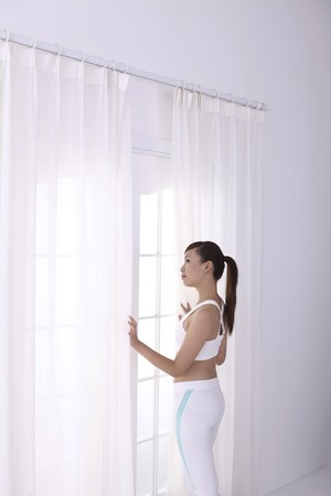 Woman in sports attire staring out the window Stock Photo - 4194572