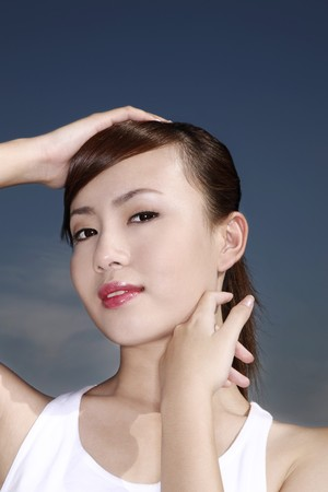 Woman with one hand on her head and another touching her cheek Stock Photo - 4194603