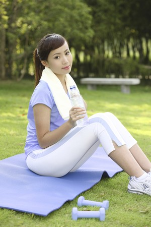 Woman holding water bottle after exercising in the park photo