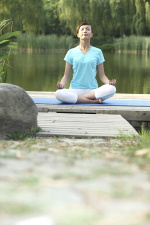 Woman meditating in the park photo