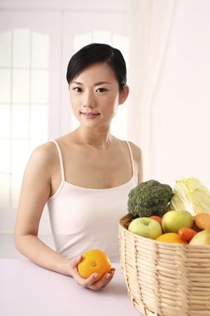 Woman holding orange with a basket of fruits and vegetables on the table photo