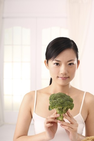 Woman holding broccoli Stock Photo