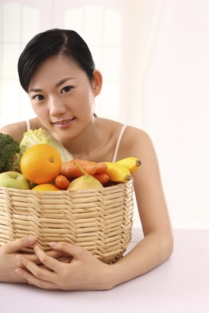 Woman hugging a basket of fruits and vegetables photo