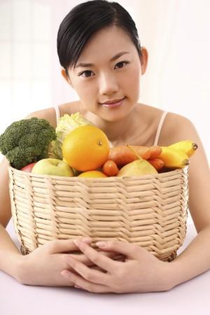 Mujer abrazando a una cesta de frutas y hortalizas Foto de archivo - 4194338