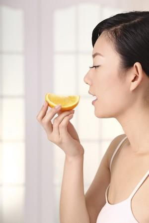 Woman holding sliced orange