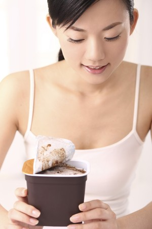 Woman holding a tub of ice-cream Stock Photo