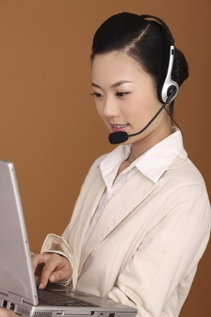 Businesswoman with headset using laptop photo