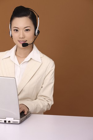 Businesswoman with headset using laptop Stock Photo