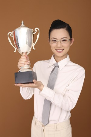 necktie: Businesswoman holding trophy Stock Photo