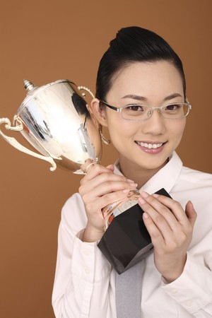 Businesswoman holding trophy Stock Photo - 4197618