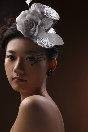 Woman with unique make-up wearing silver hat photo