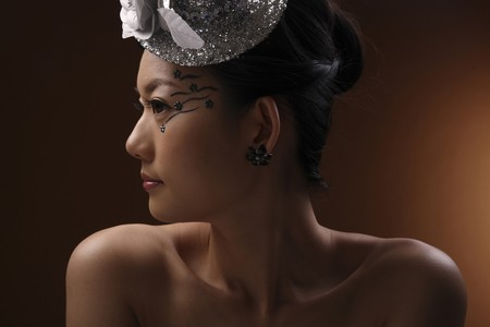 Woman with unique make-up wearing silver hat Stock Photo