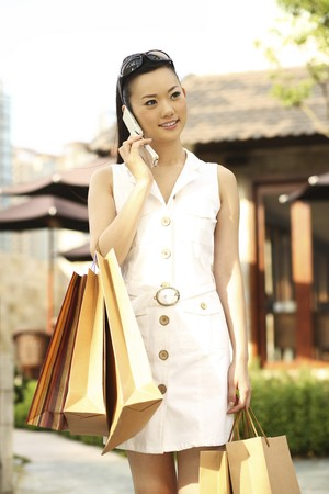 contentment: Woman with shopping bags talking on the phone Stock Photo
