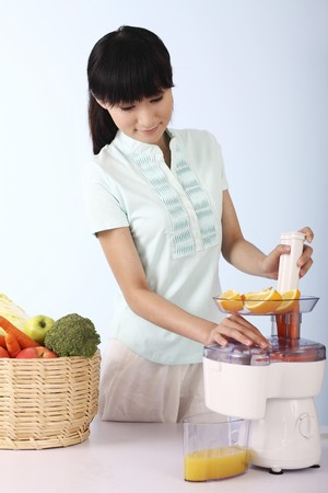 Woman making orange juice Stock Photo - 4197518