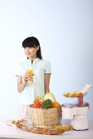Woman looking away while holding a glass of orange juice Stock Photo